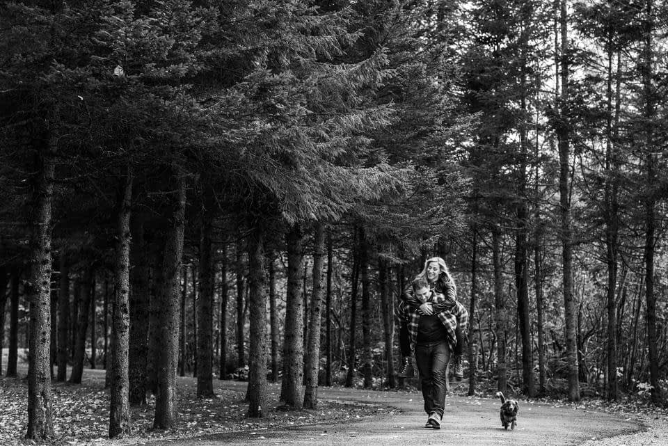 Man giving a piggy back ride to his fiancee with dog running along beside 02