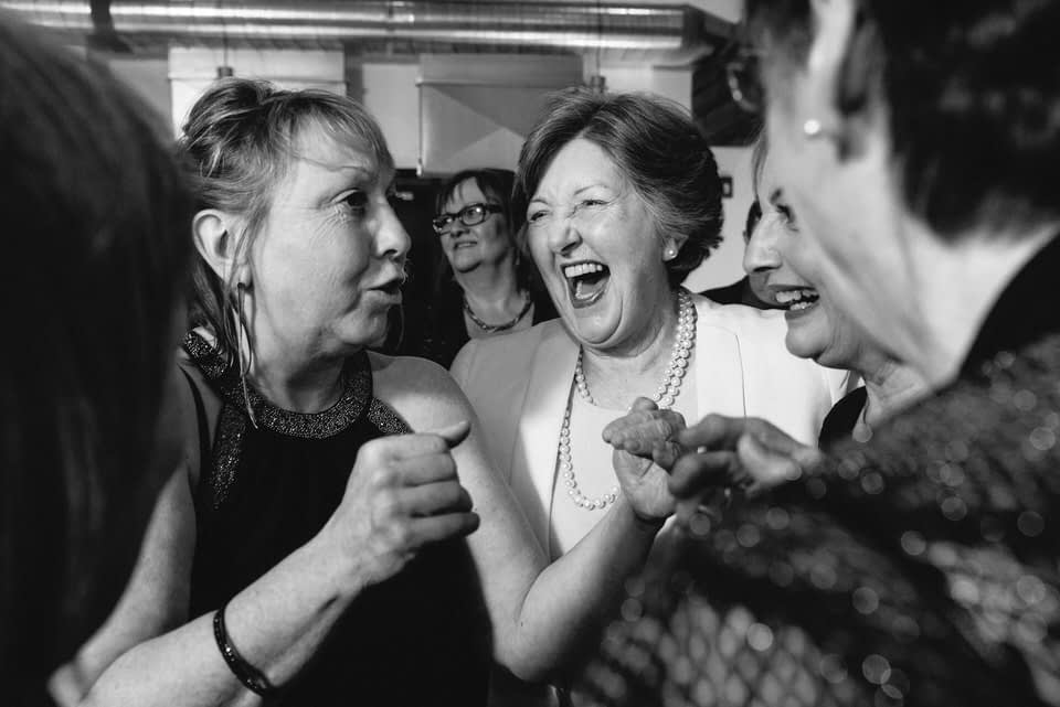 Guests laughing together at wedding reception