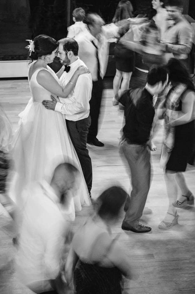 Blurry long exposure of bride and groom still on the dance floors as others move around them