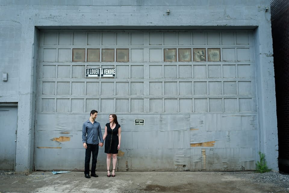 Engagement photo in front of grungy garage doors in Griffintown