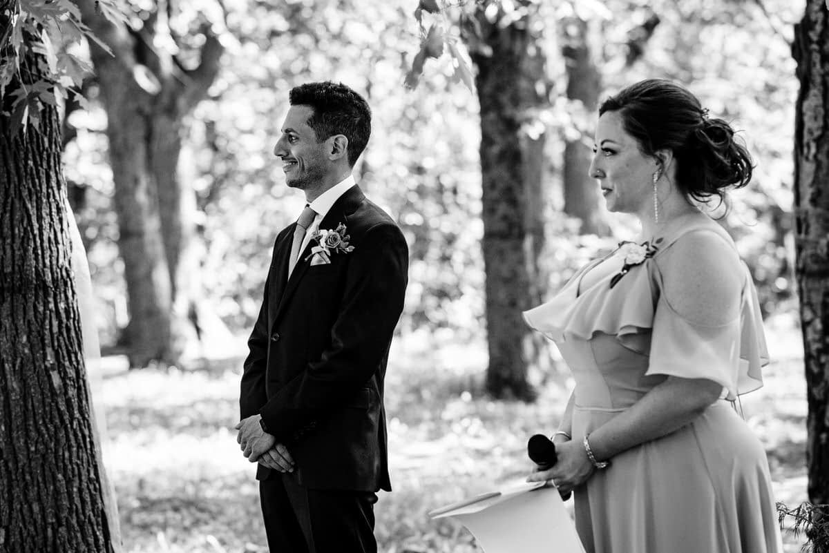 Groom and wedding officiant watching bride arrive