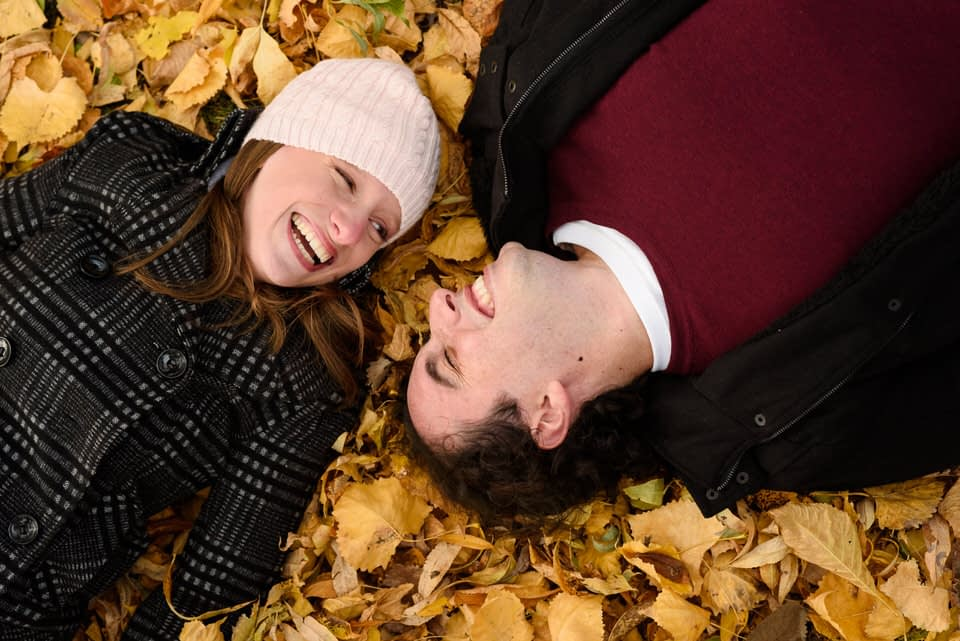 couple lying in a bed of fallen leaves