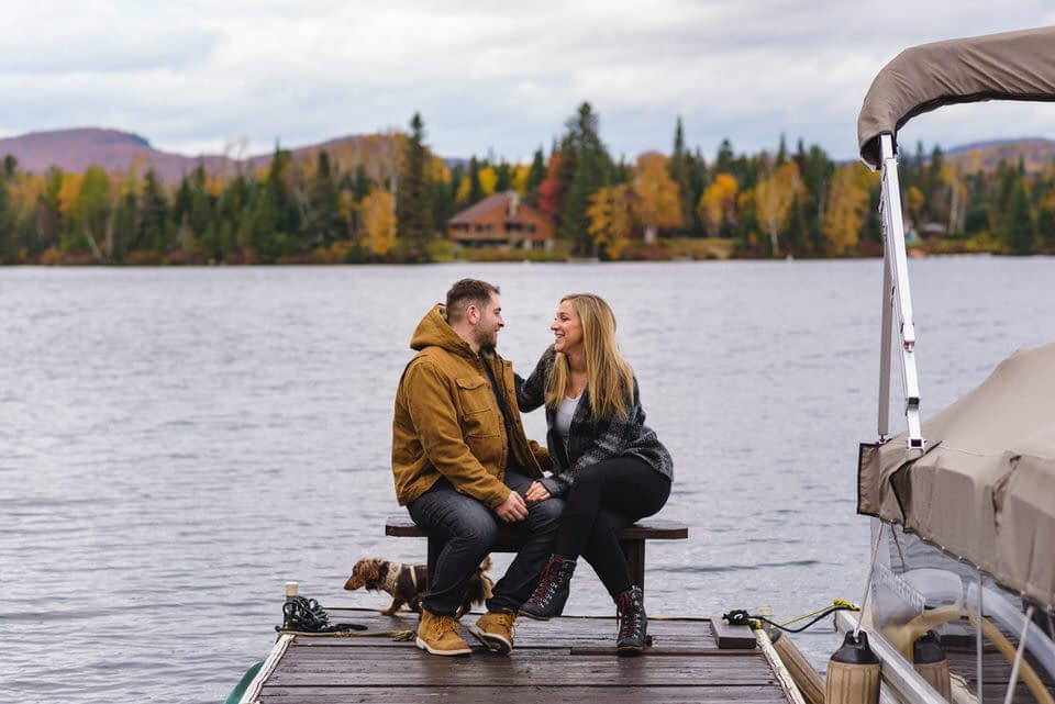 Couple cuddling on a dock while their dog looks at the lake