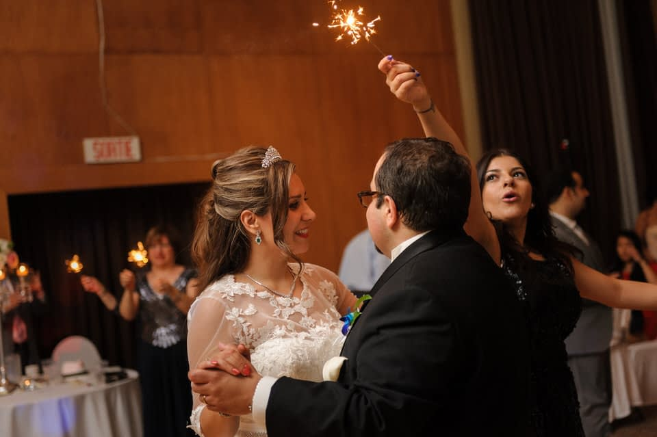 Wedding guest waving a lit sparkler around the bride and groom during their dance
