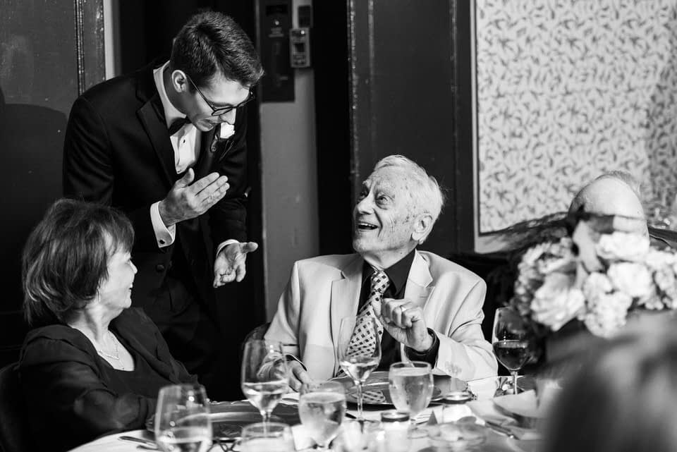 Groom chatting with relatives at wedding