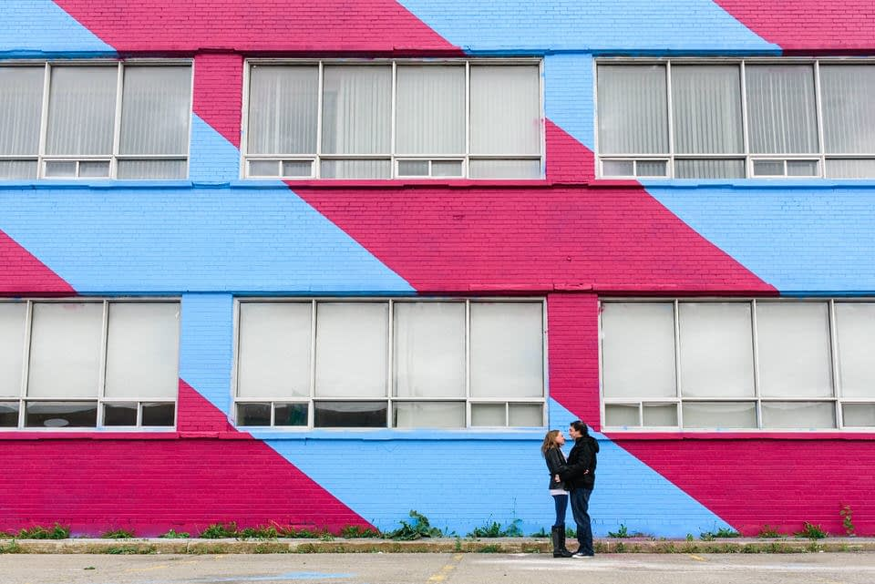Couple holding each other in front of bleu and pink graffiti mural in Montreal