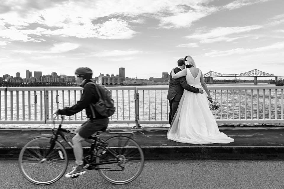 bike goes by as wedding couple enjoys the view of Montreal from the bridge
