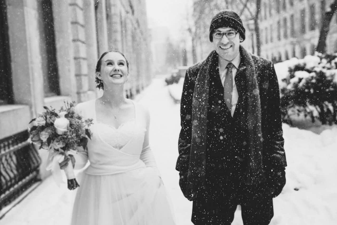 Bride and groom staring at snow floating down