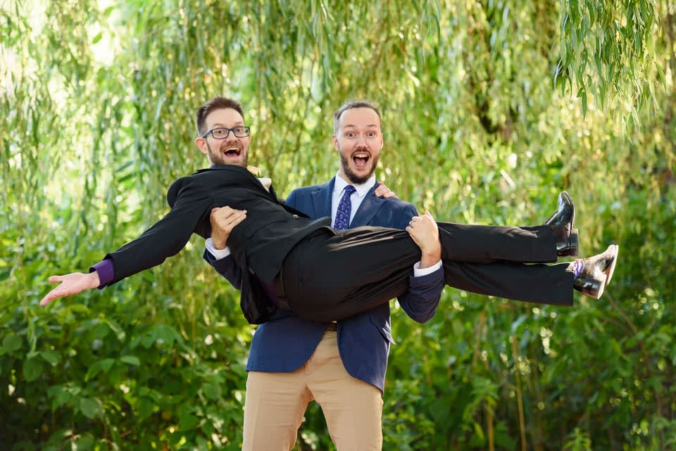 Silly photo with groomsman lifting groom