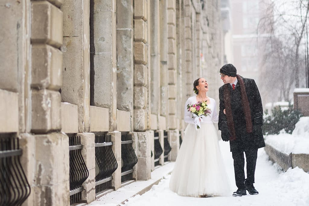 Bride and groom in winter snow in Old Montreal
