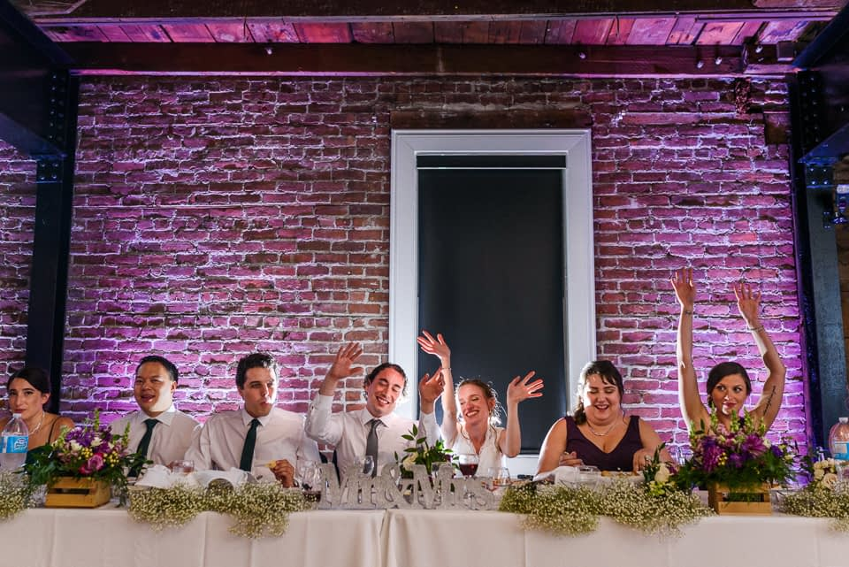 Wedding party singing a song at dinner at Canvas Loft Reception hall