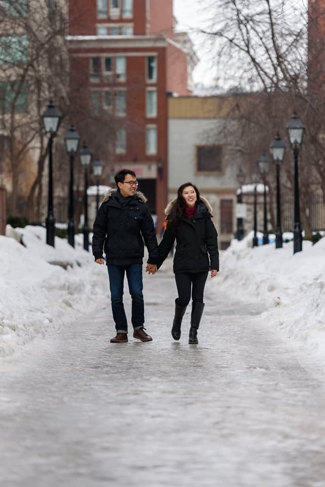 Winter engagement photo of couple walking hand in hand