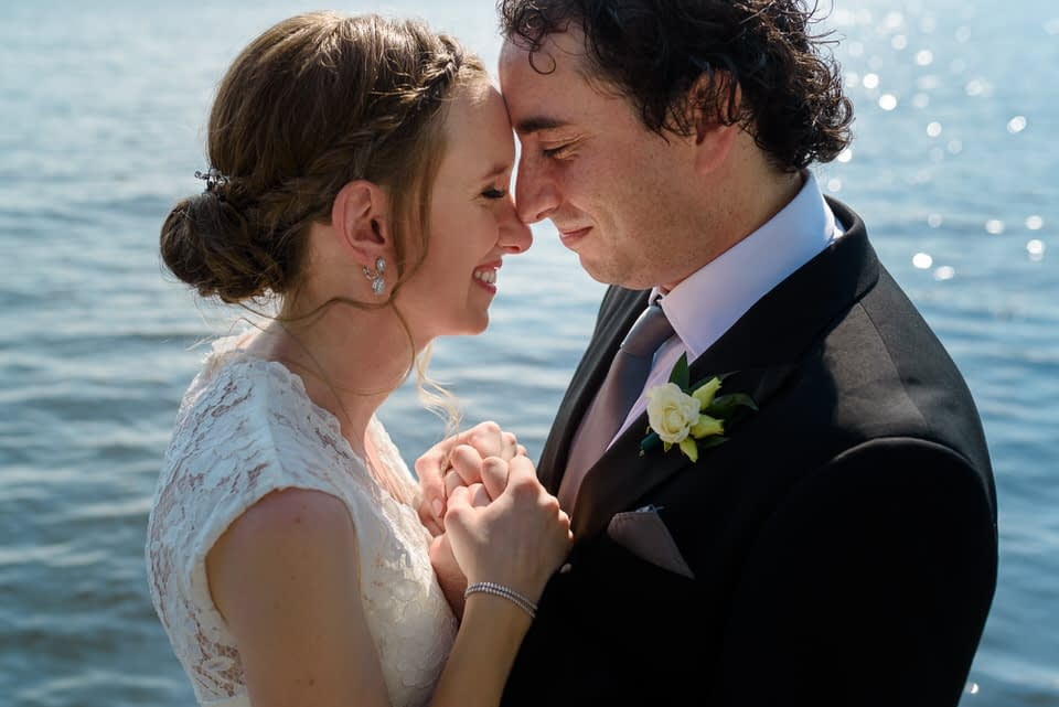 Wedding portrait of couple leaning close together at a lake