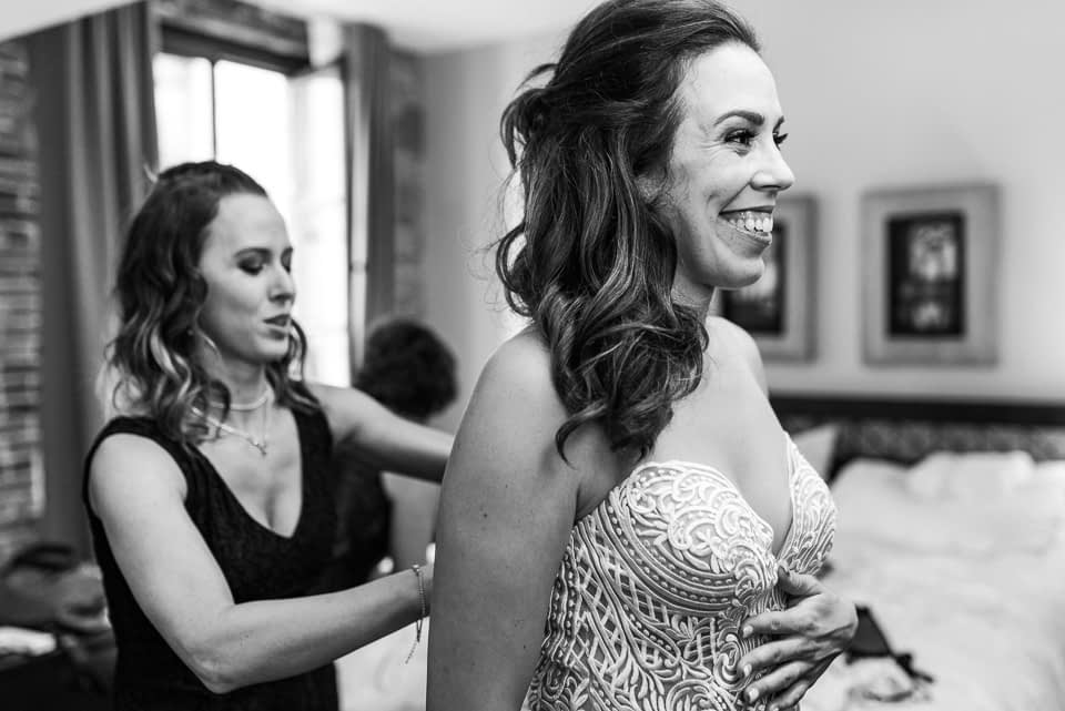Happy bride getting wedding dress buttoned up