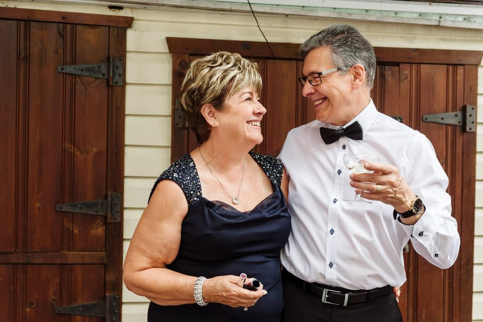 Bride's parents smiling at each other in back yard