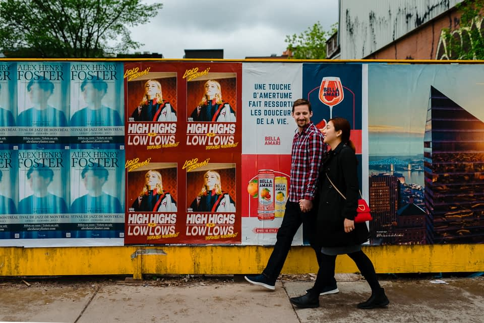 Couple strolling by wall of concert posters