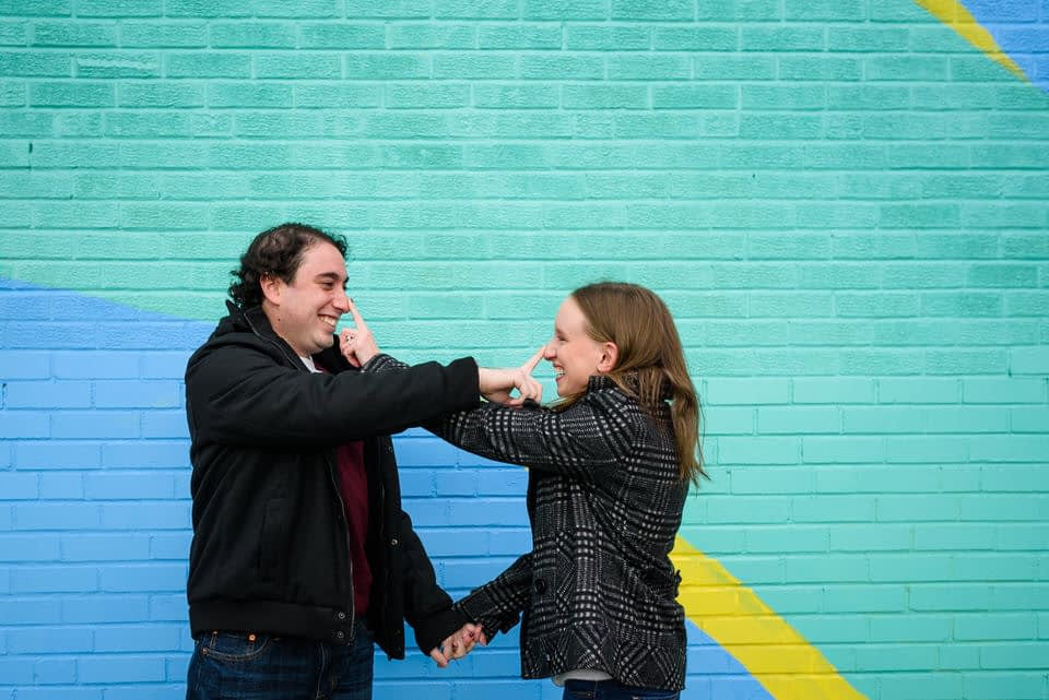 Engaged couple teasing each other in front of graffiti mural