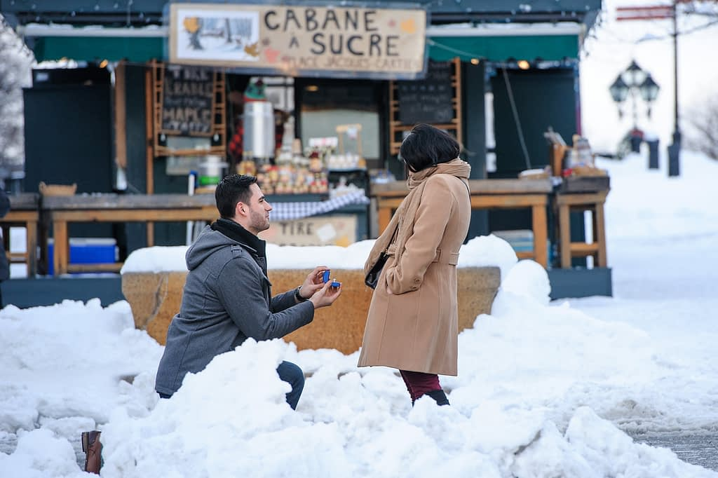 Man kneeling in the snow to propose to his girlfriend