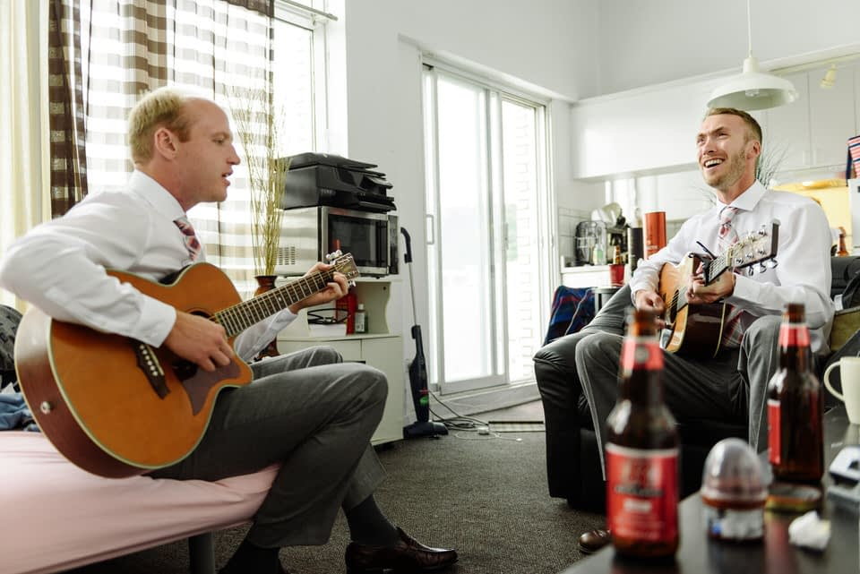 Groomsmen practicing a song on the guitar