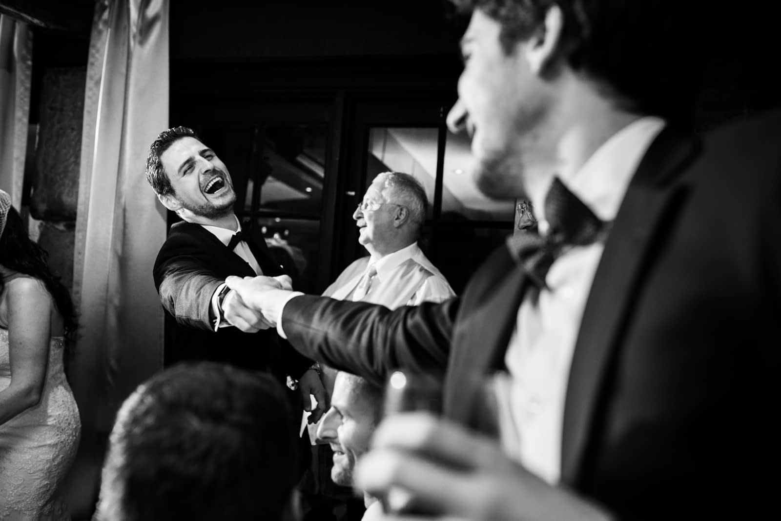 Laughing groom shaking hands with friend
