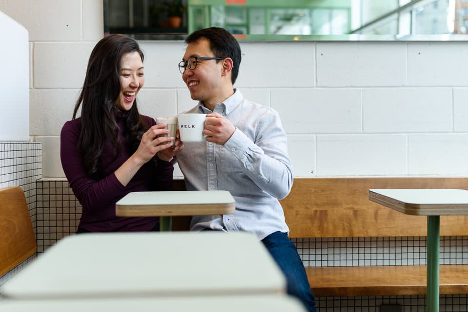 Engaged couple toasted with coffee mugs at Melk Cafe Bar