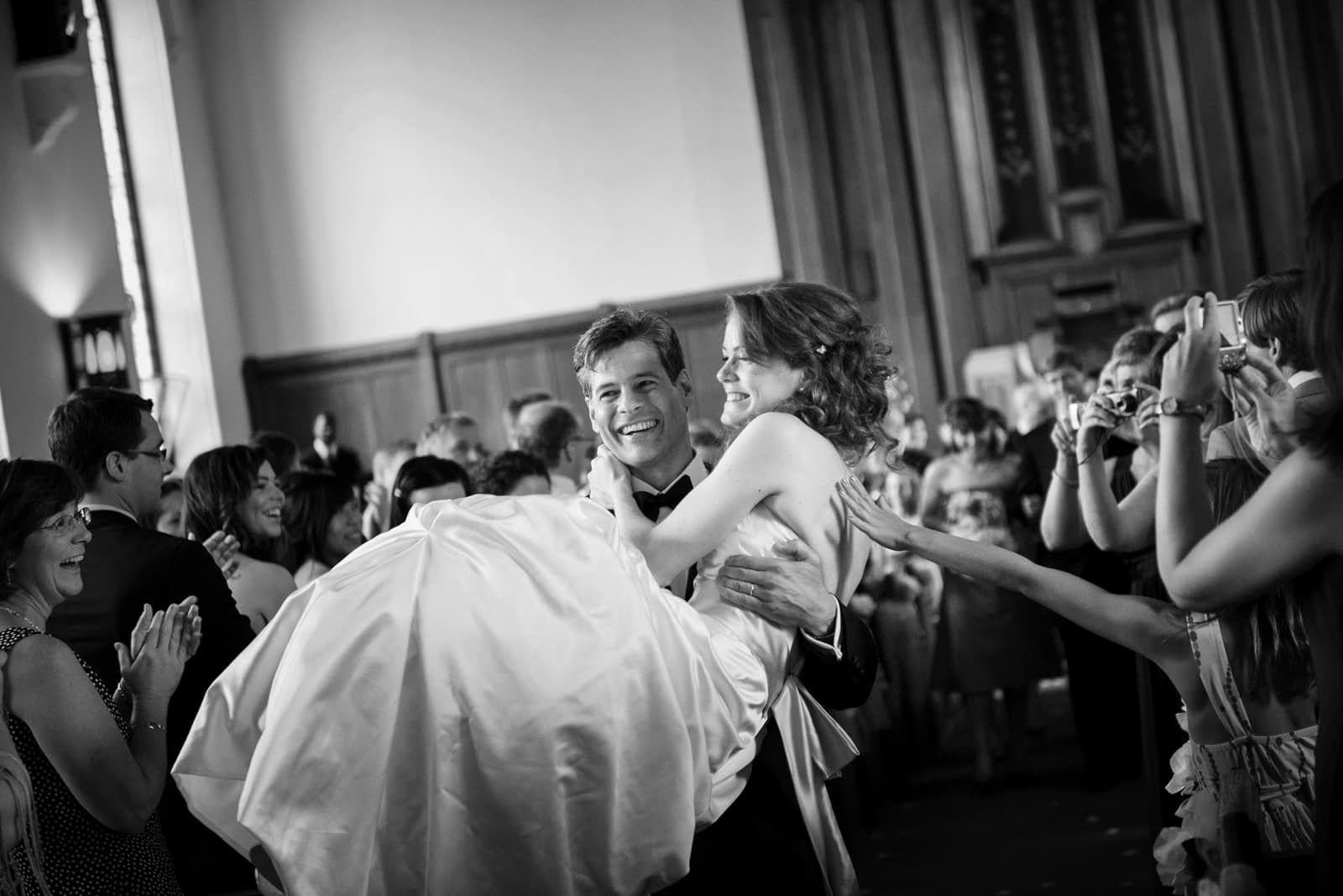 Groom carrying bride down aisle and a guest's hand reaches out to touch her from the crowd
