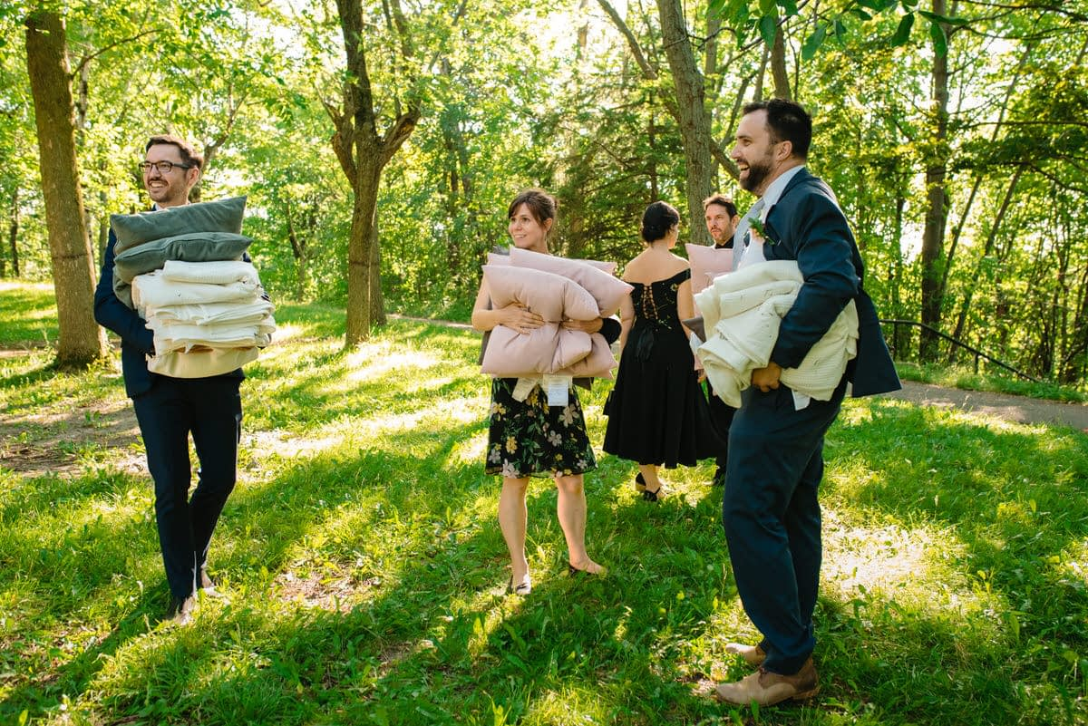 Friends carrying away cushions and blankets from the wedding in a park