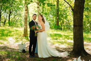 Bride and groom look around at trees in park wedding