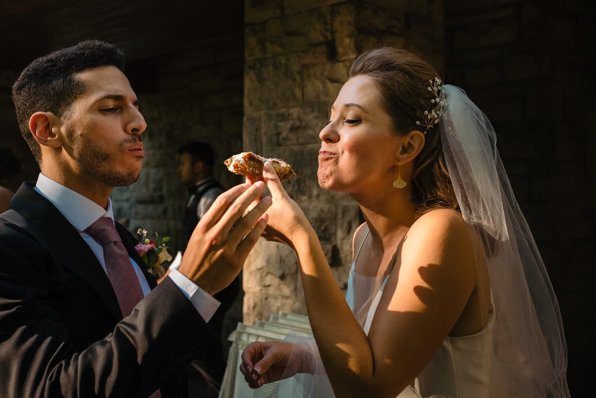 Bride and groom sharing a cannoli during cocktail hour in park