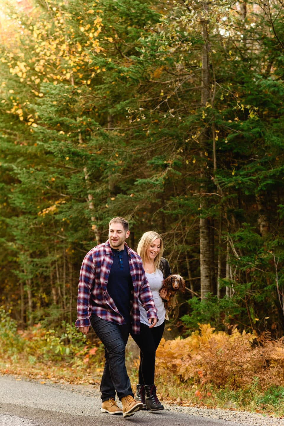 Engaged couple walking in the woods carrying their puppy