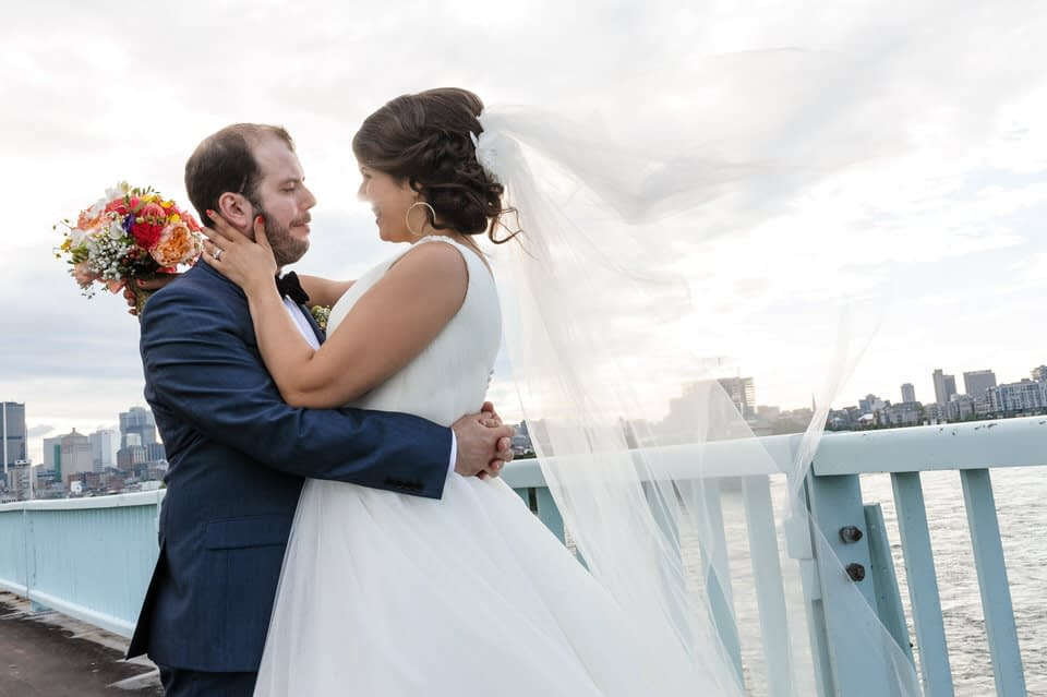 Bride and groom on a bridge with Montreal skyline behind them