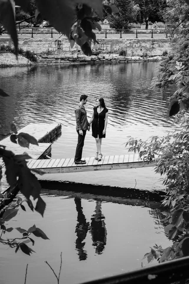 Couple standing on a dock with their reflection in the water of Lachine Canal