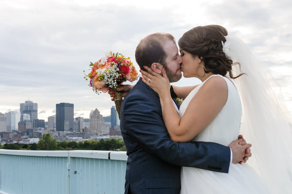 Bride and groom kissing on a bridge with view of Montreal behind them