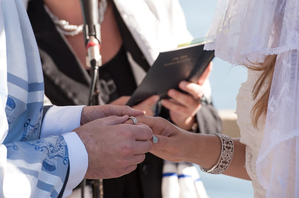 Groom putting on ring at wedding