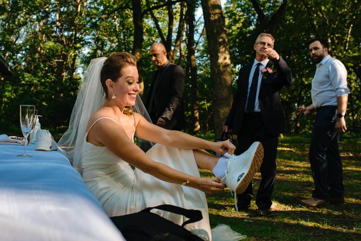 Bride putting on running shoes for her wedding photos in the park