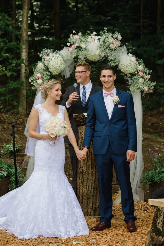 Bride and groom holding hands in front of floral archway at outdoor wedding