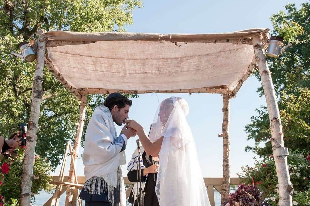 Groom drinking from cup under huppah