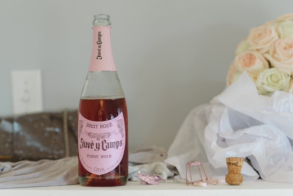 Opened bottle of rosé and a cork