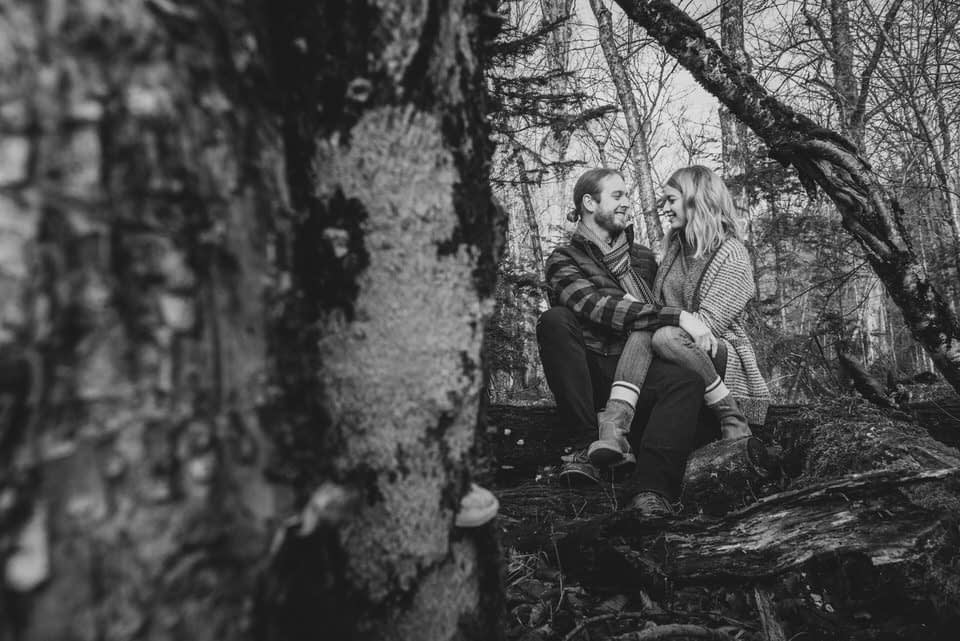 Couple sitting on a log in the woods