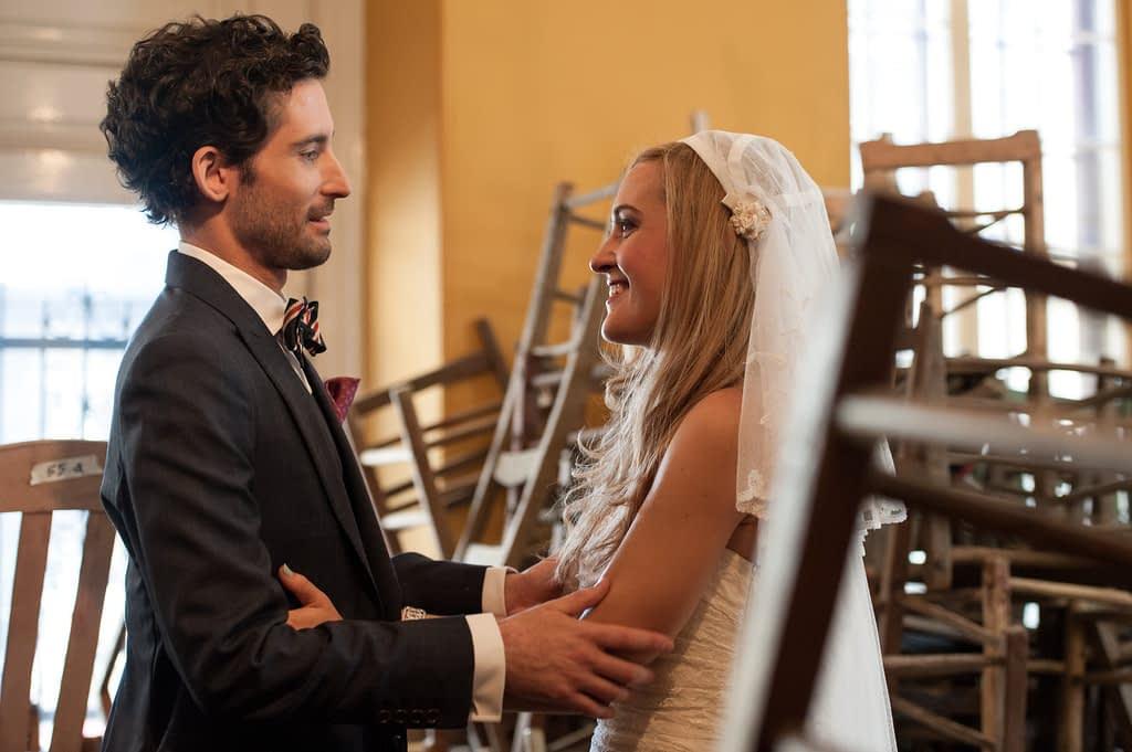 Wedding couple in room full wooden chairs