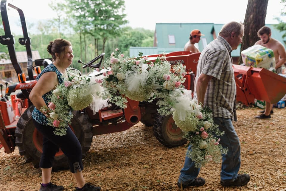 Man and woman carrying an arch of wedding flowers up the hill past a tractor