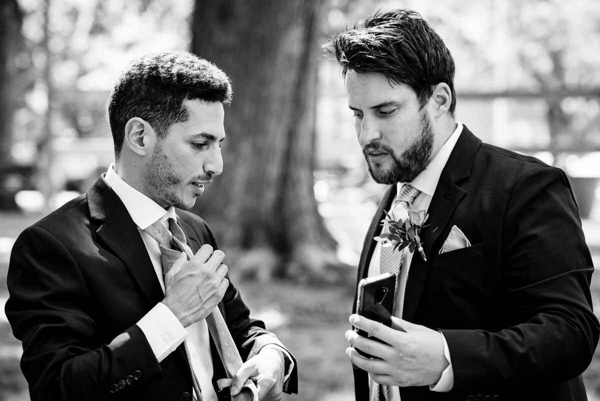 Friend holding phone so the groom can tie his tie