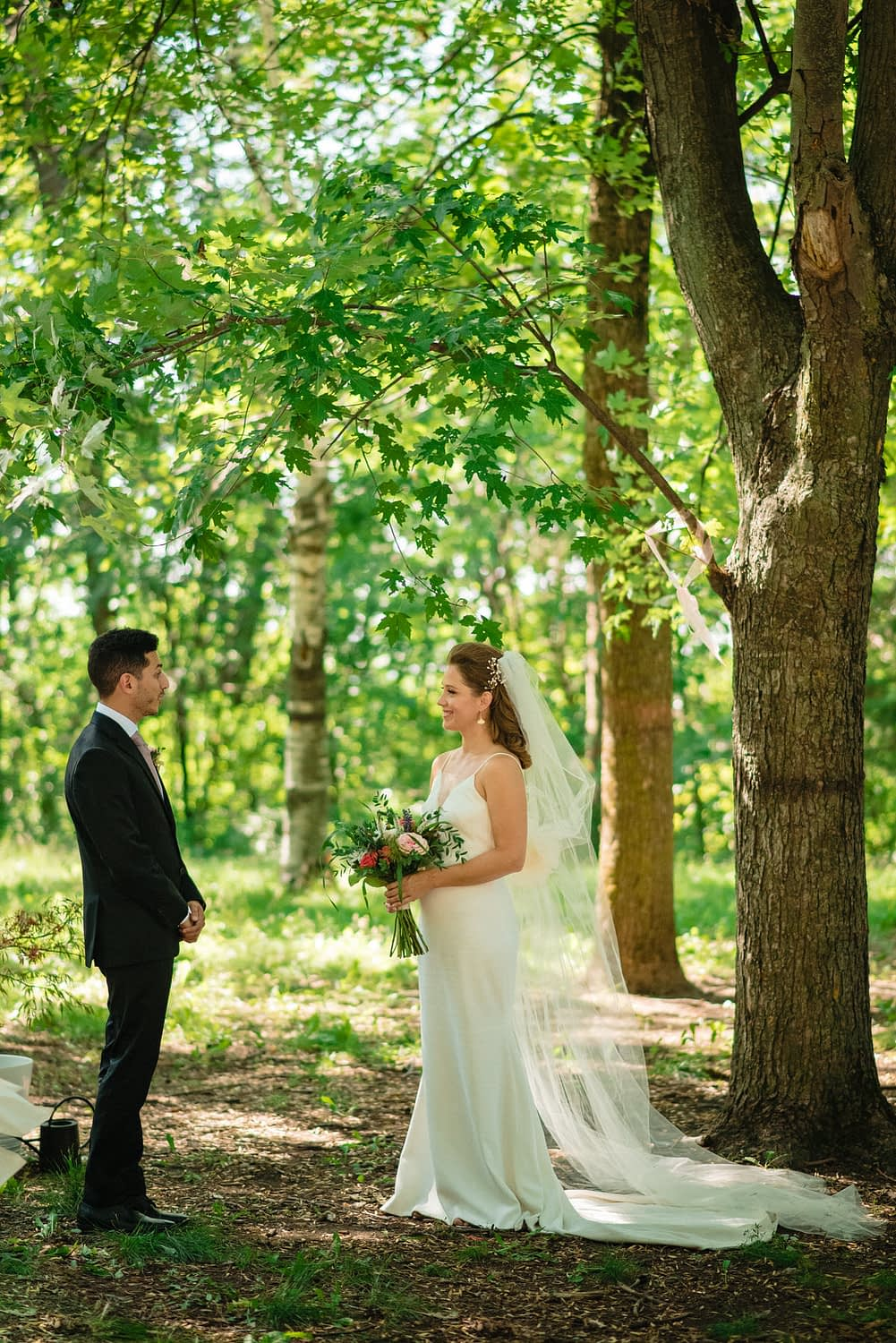 Wedding couple standing under tree in park wedding during the pandemic