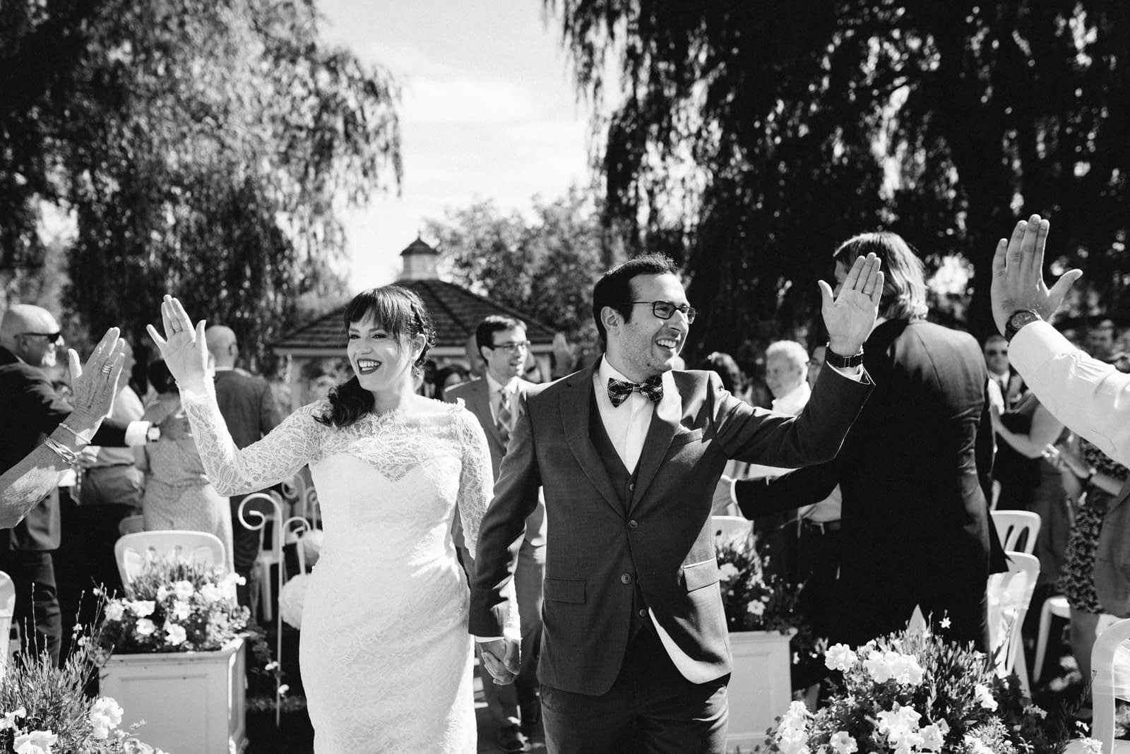 Bride and groom high fiving wedding guests as they walk down the aisle