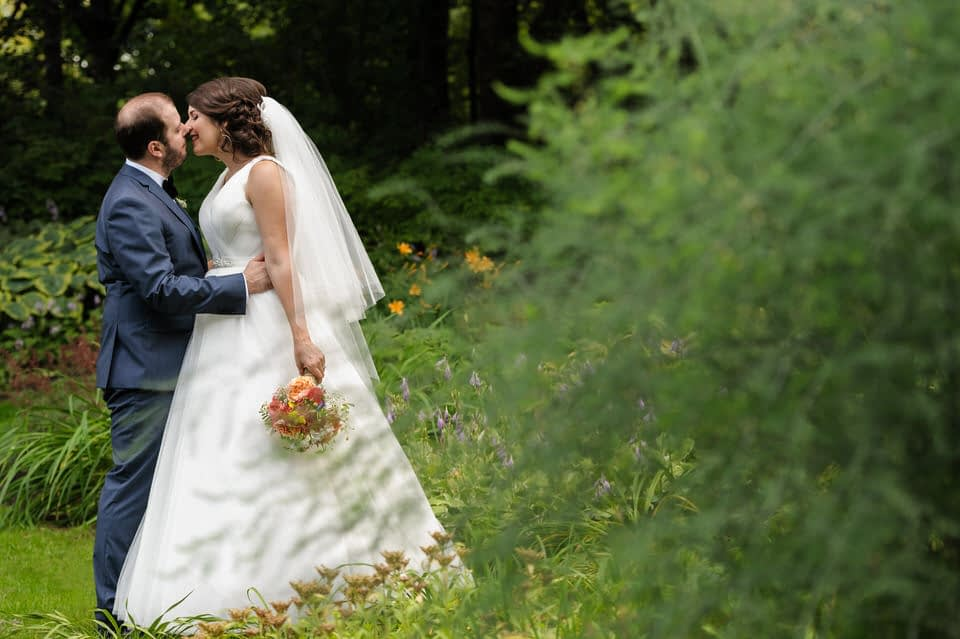 Bride and groom kissing framed by lush greenery