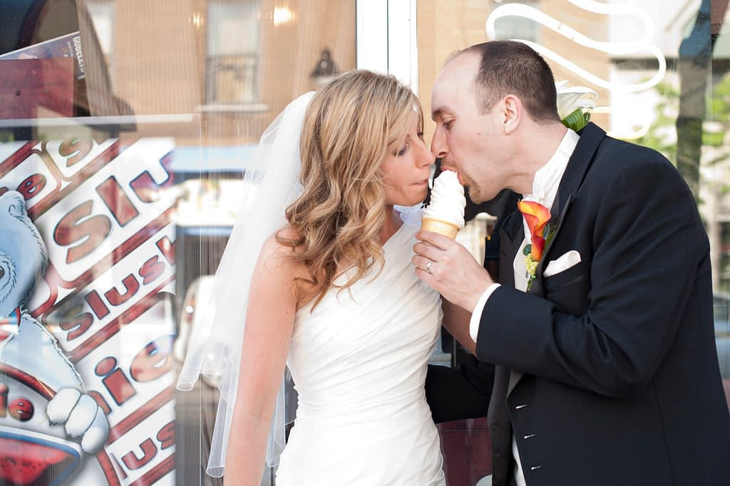 Bride and groom eating ice cream on the street