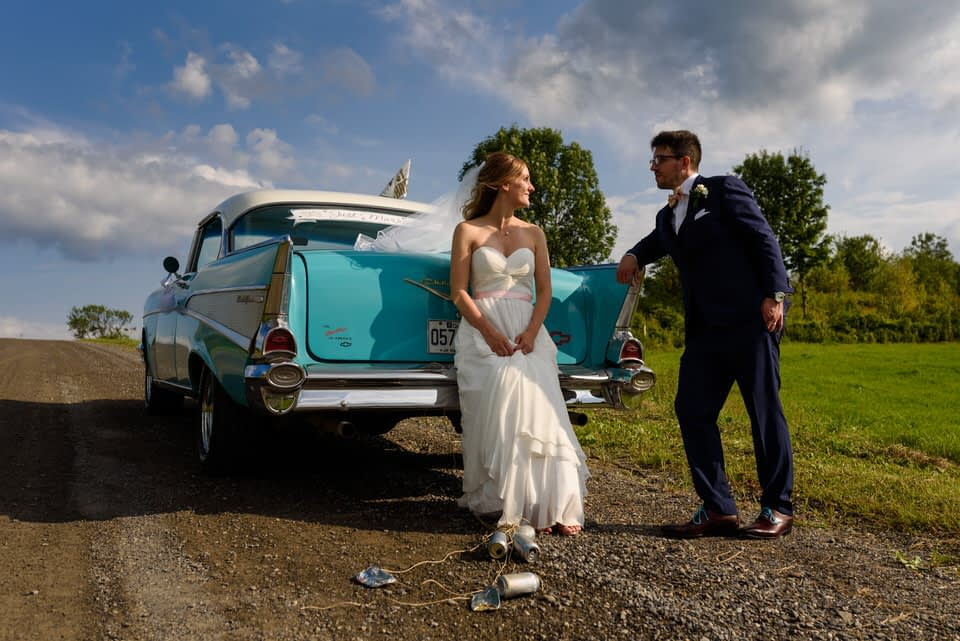 Portrait of bride and groom leaning on the back of a turquoise vintage car