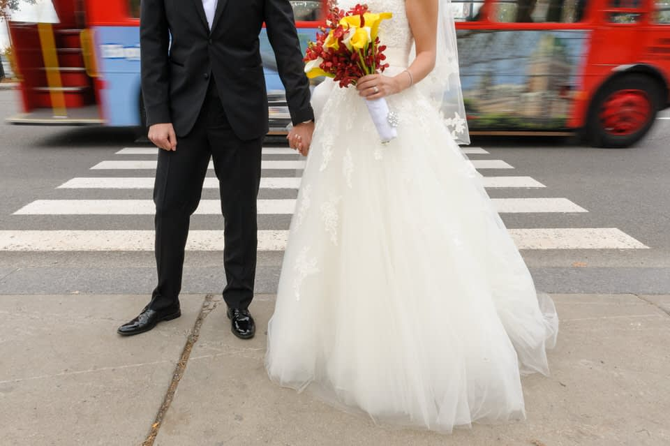 Bride and groom standing in front of a crosswalk with blurry traffic behind