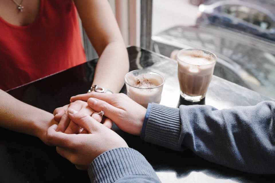 Engaged couple holding hands in coffeeshop