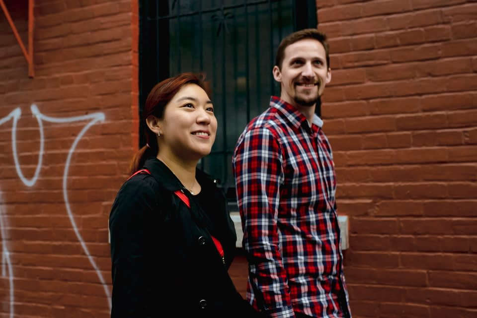 Couple walking in alleyway with brick wall behind